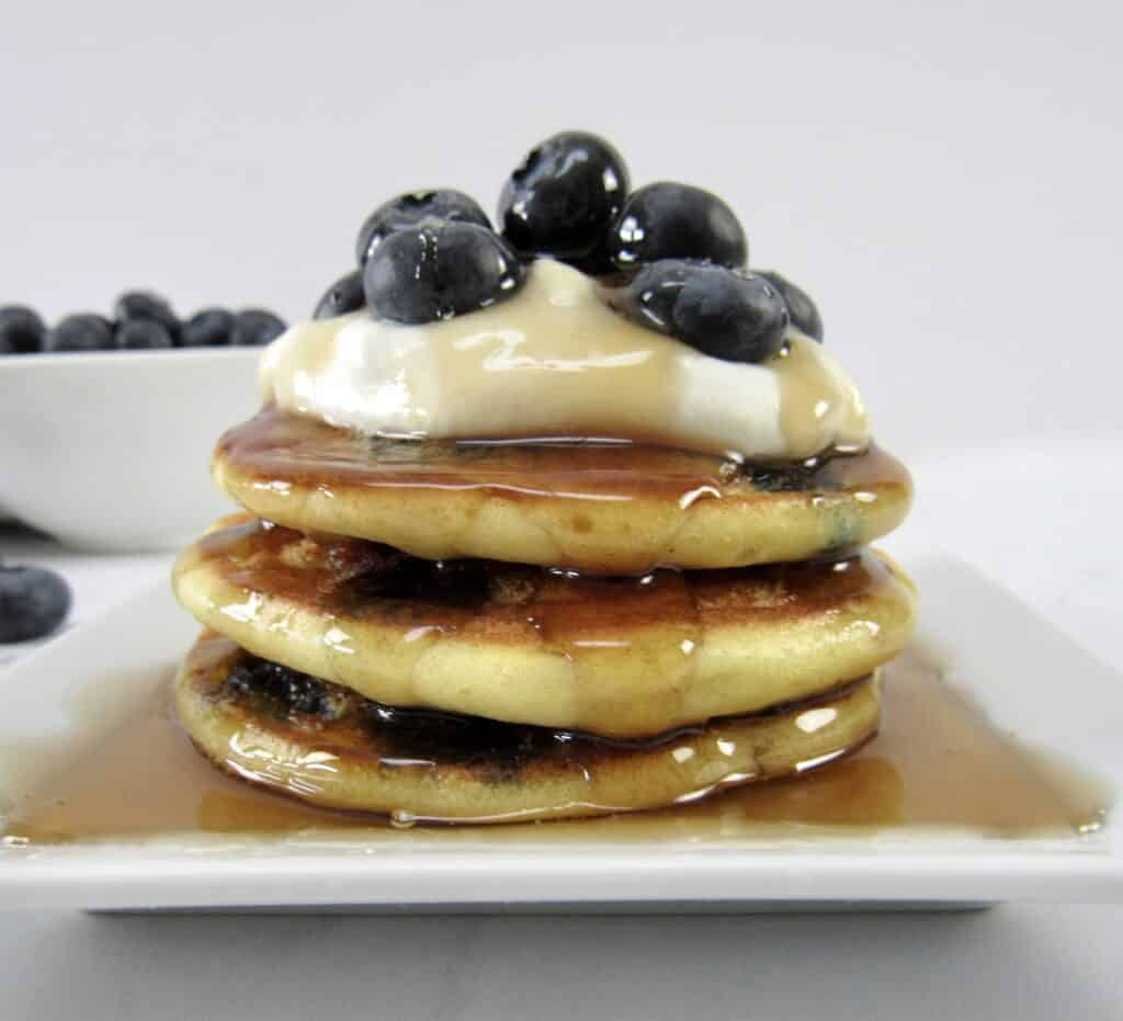 blueberry pancakes with syrup and blueberries on top closeup