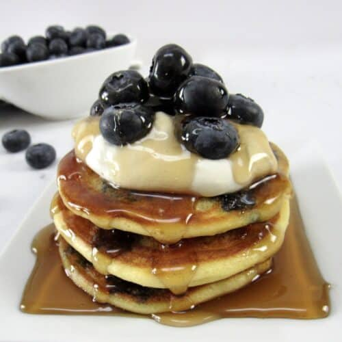 blueberry pancakes with syrup and blueberries on top
