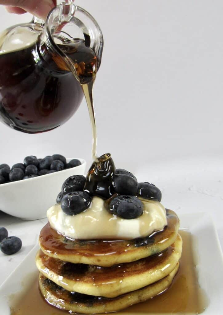 blueberry pancakes on plate with syrup being poured over top