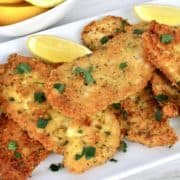 Keto Chicken Milanese on white plate with lemons