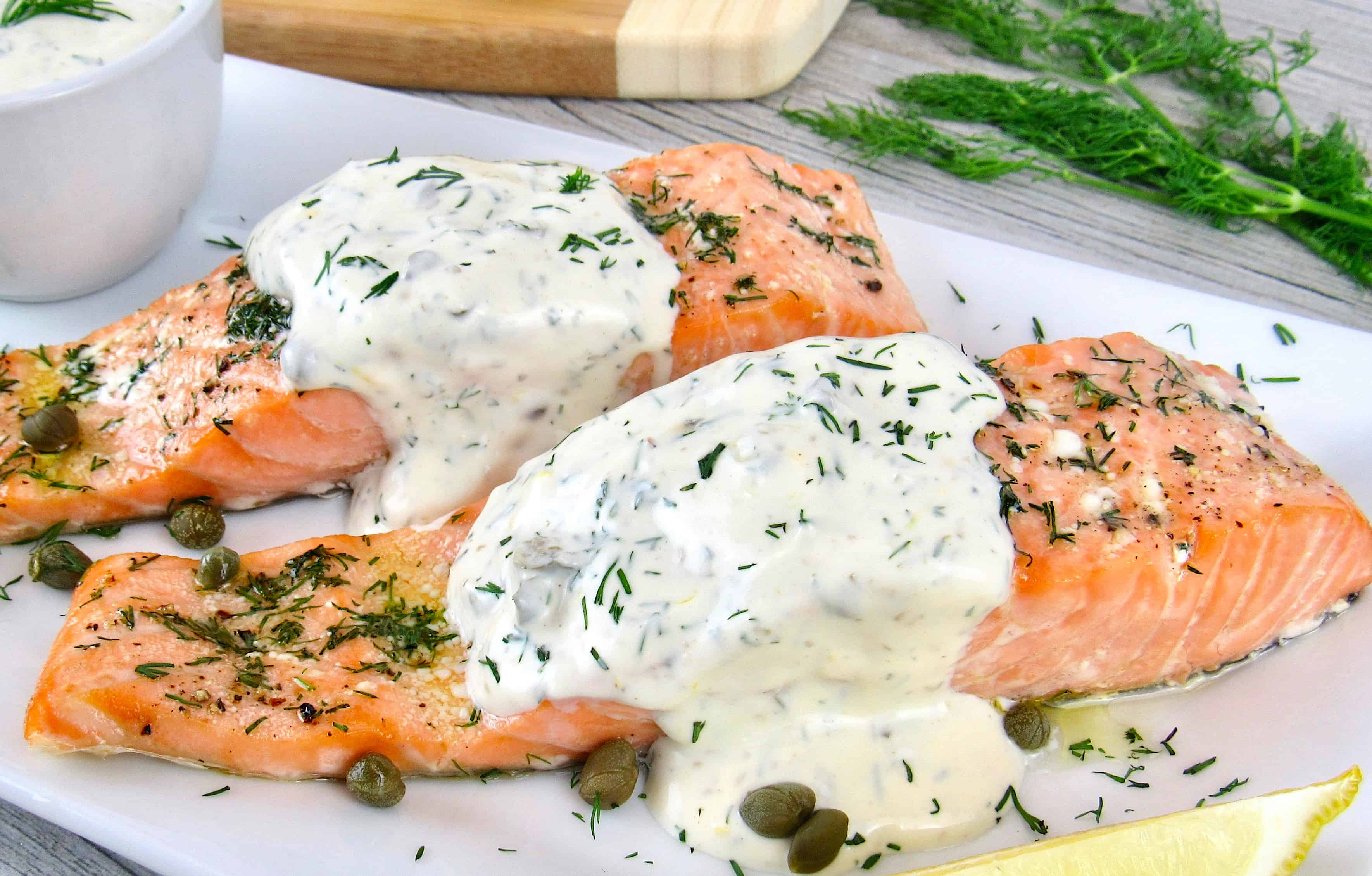 closeup of 2 pieces of salmon on white plate with dill and capers