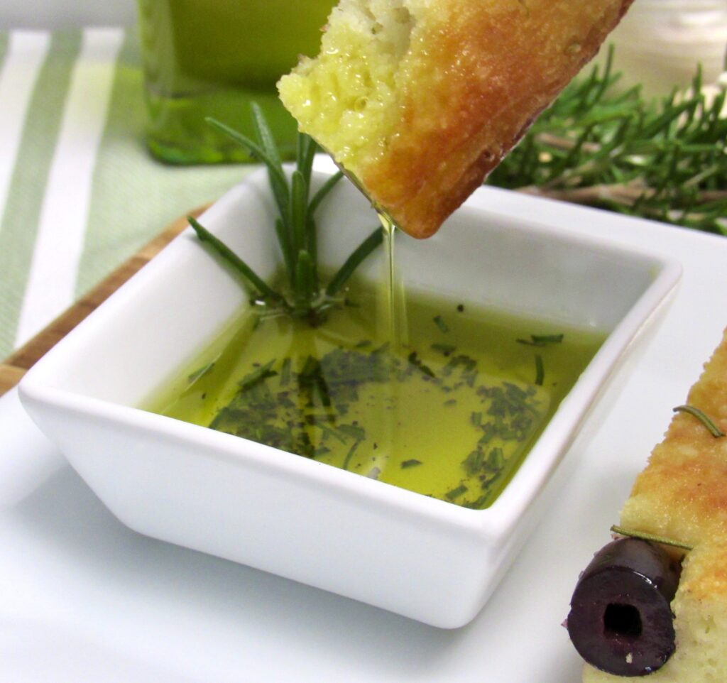 piece of Rosemary Focaccia being dipped into dish of olive oil