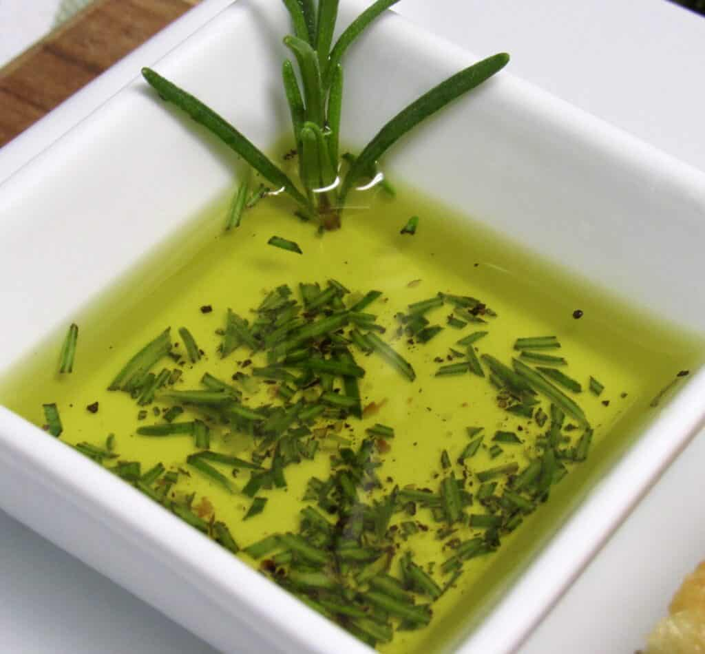 olive oil in square white cup with rosemary and pepper