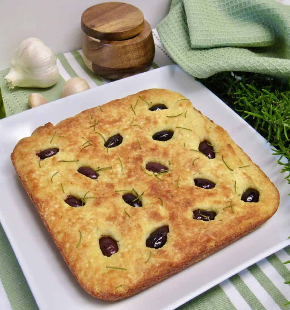 baked square loaf of rosemary focaccia on white plate