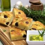 stacked up slices of rosemary and olive focaccia on cutting board