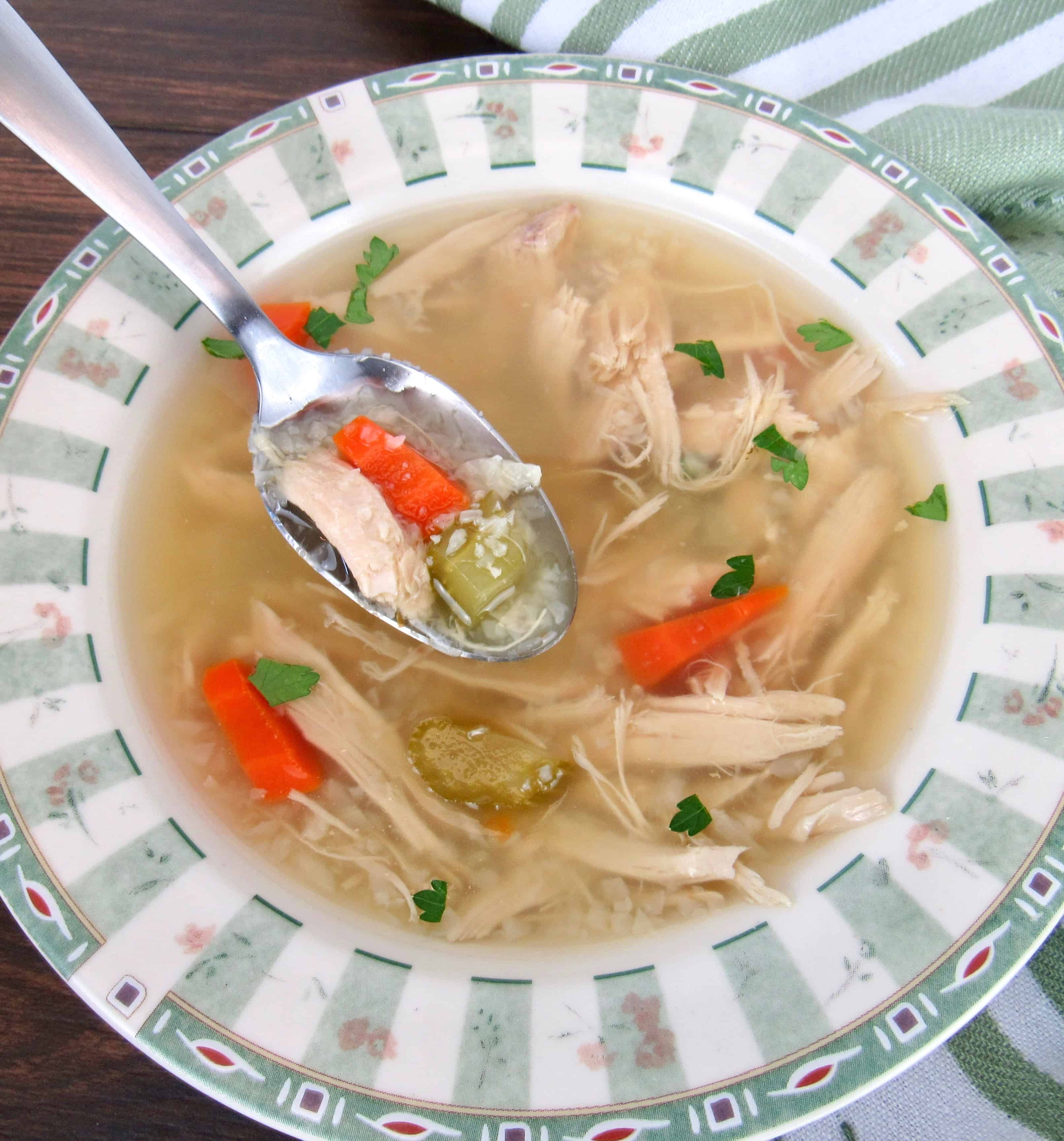 chicken soup with spoon holding up soup over the bowl