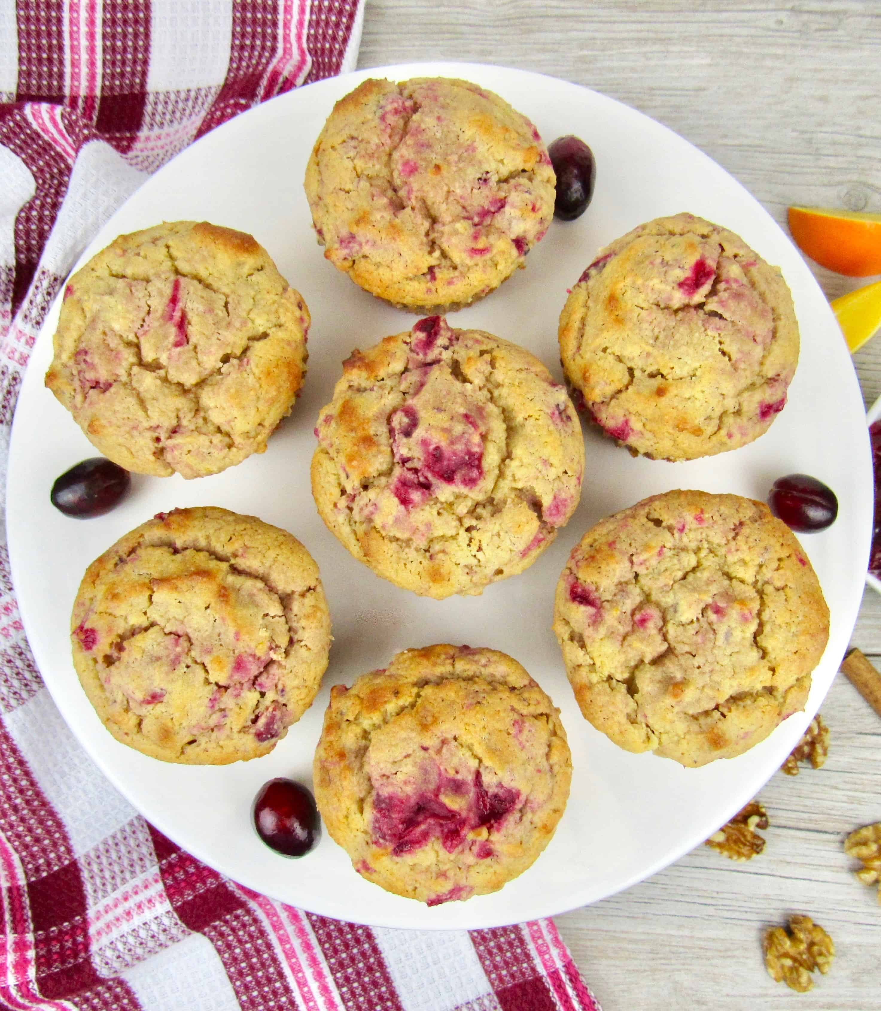 overhead view of 7 cranberry walnut muffins on white plate