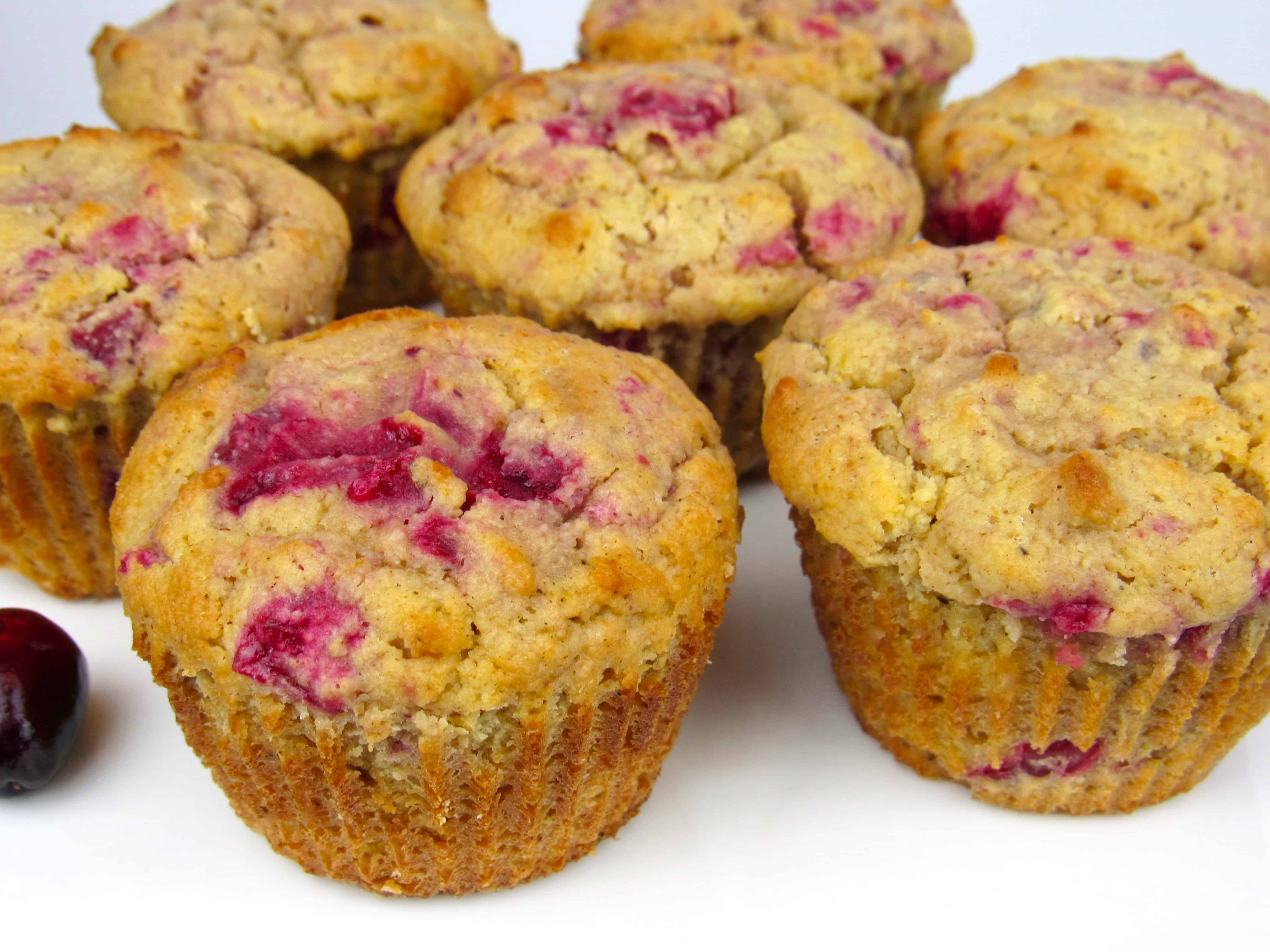 closeup of cranberry sauce walnut muffins on white plate