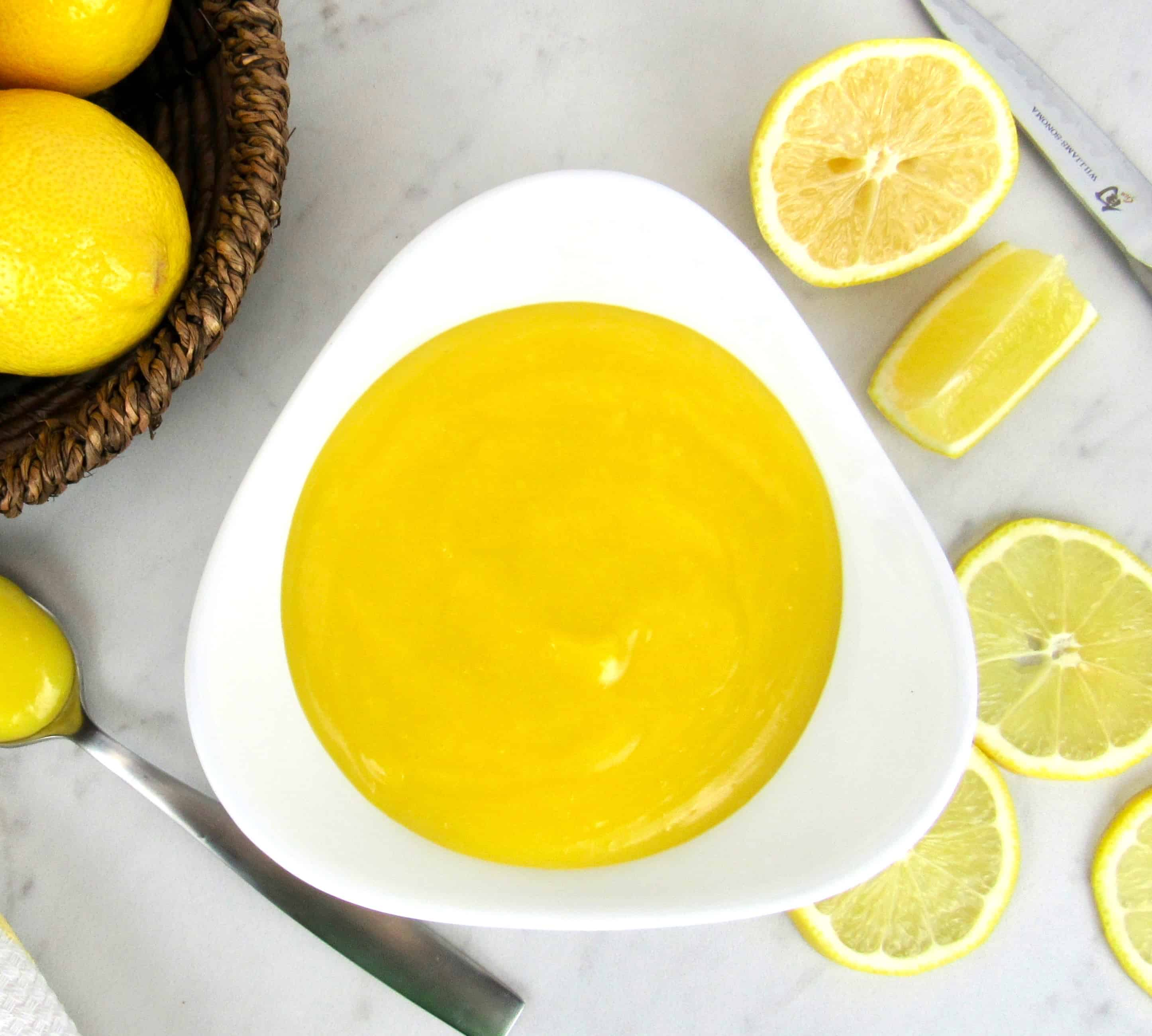 overhead view of lemon curd in white bowl with lemons in the background