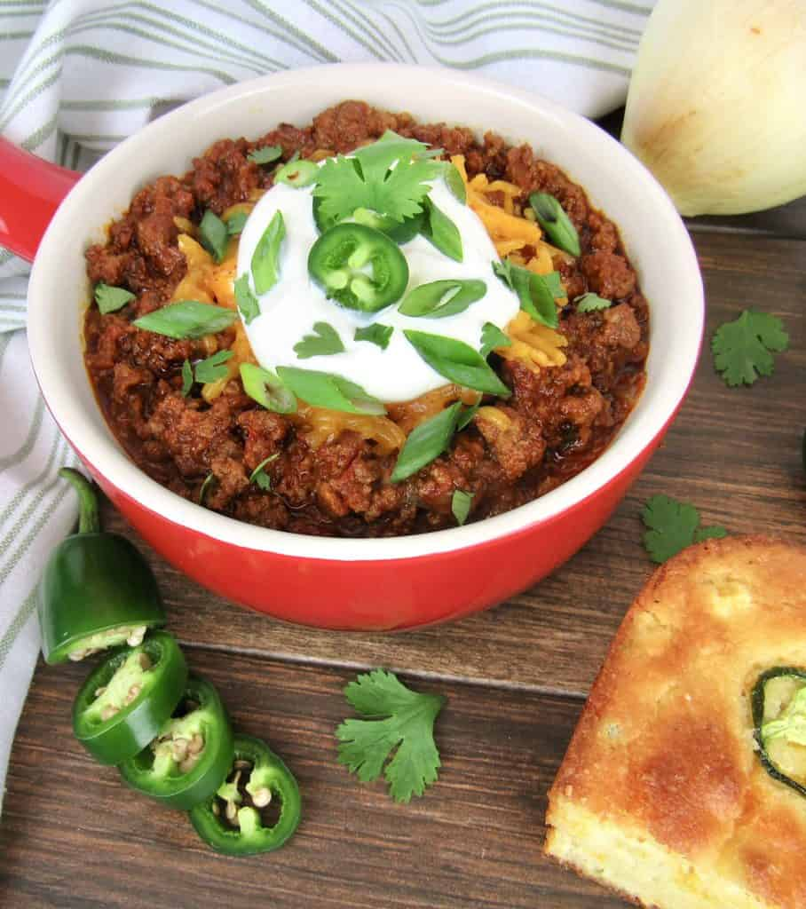 Keto No Bean Chili in red bowl with sour cream and jalapenos on top