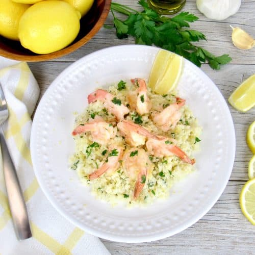 Keto and Low Carb Shrimp Scampi with Cauliflower Rice in bowl, Fork, and Lemon Slices