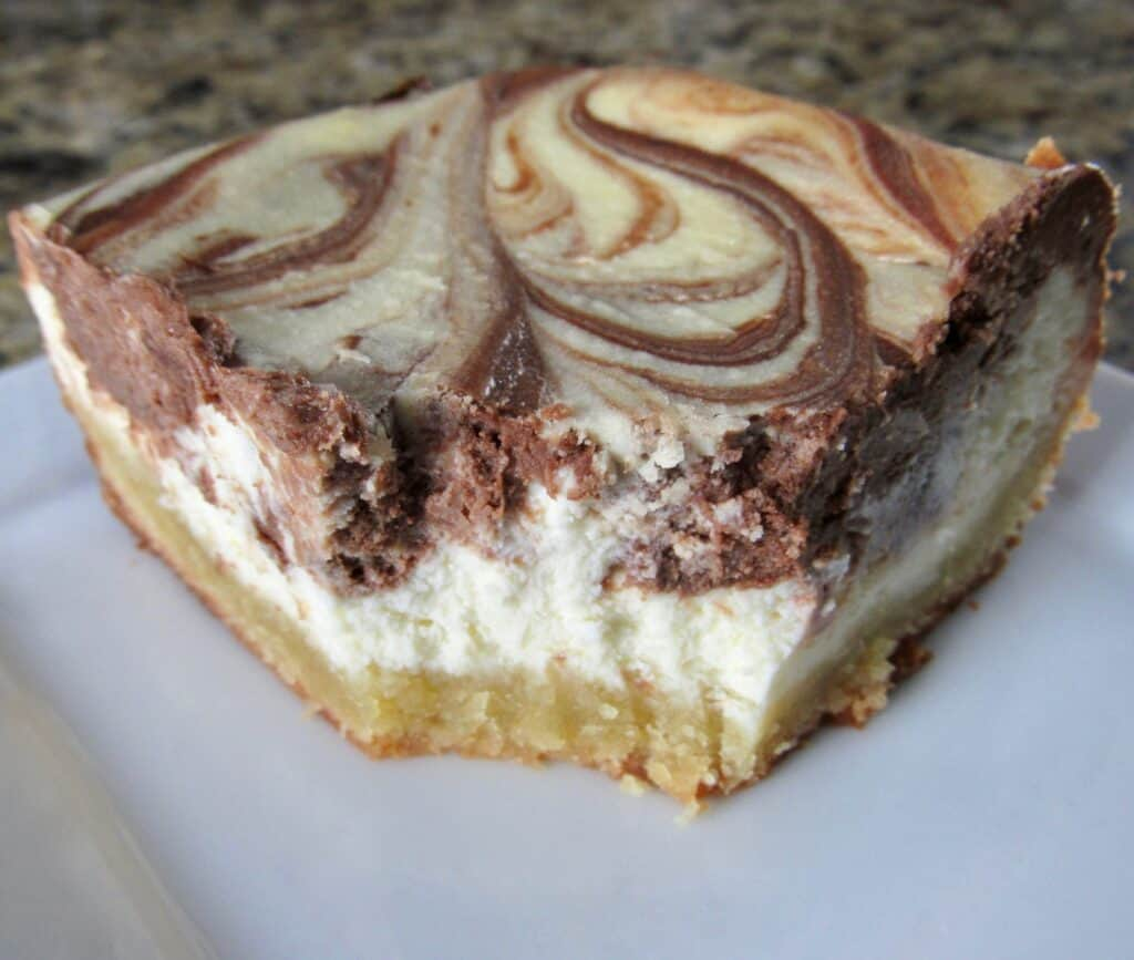 slice of vanilla and chocolate swirl cheesecake on white plate with bite taken out