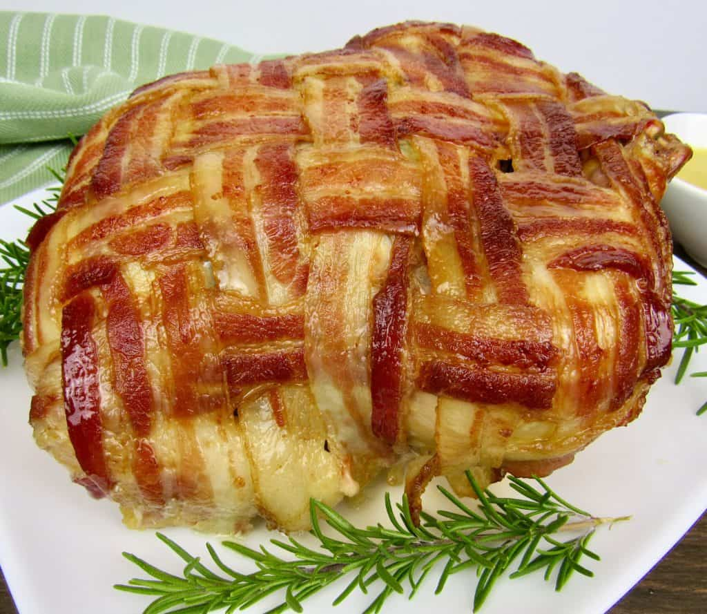 bacon wrapped whole chicken on white plate