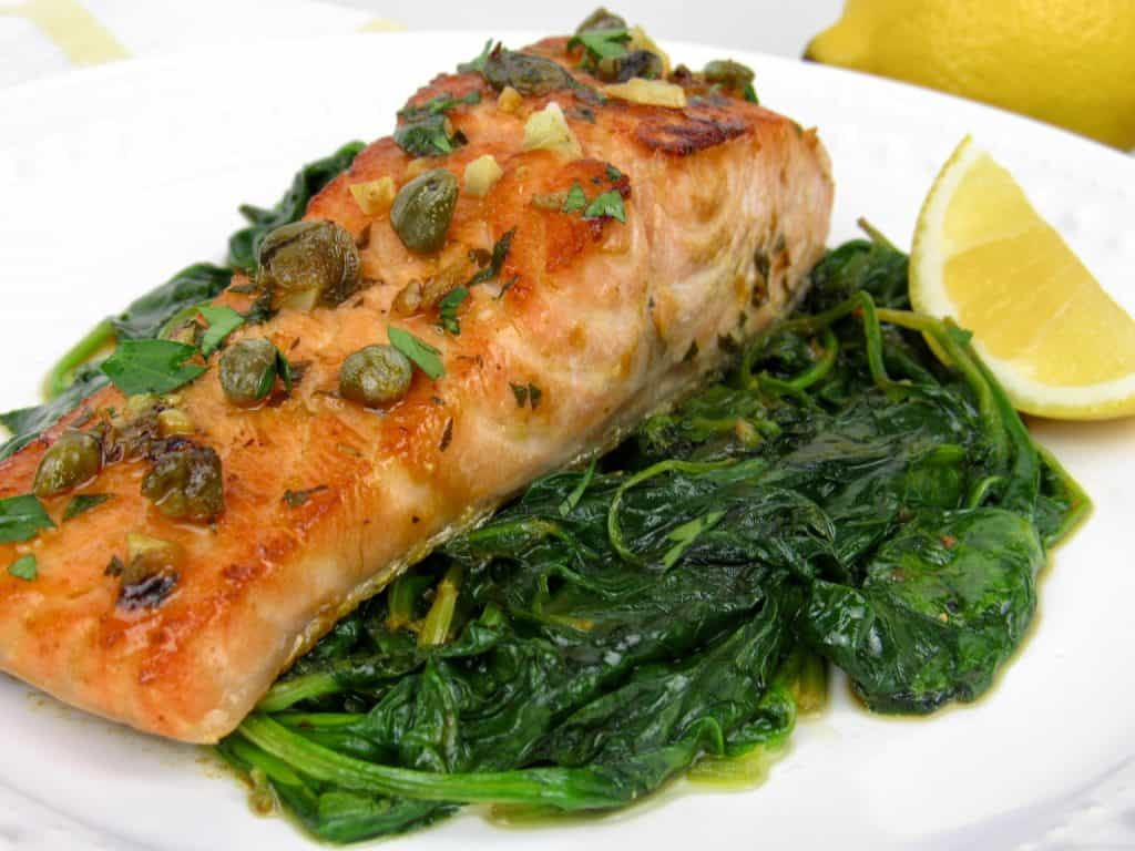 closeup of salmon piccata over spinach