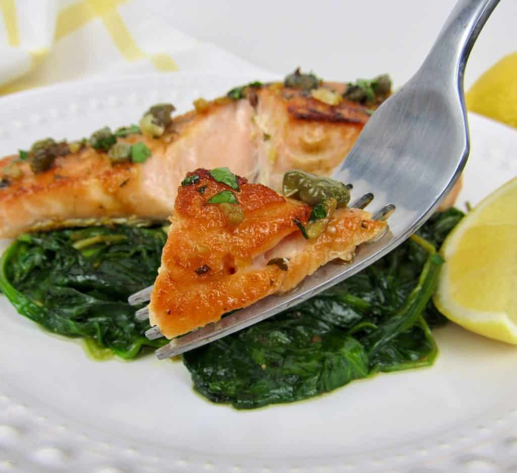 salmon with spinach on white plate with fork holding up some