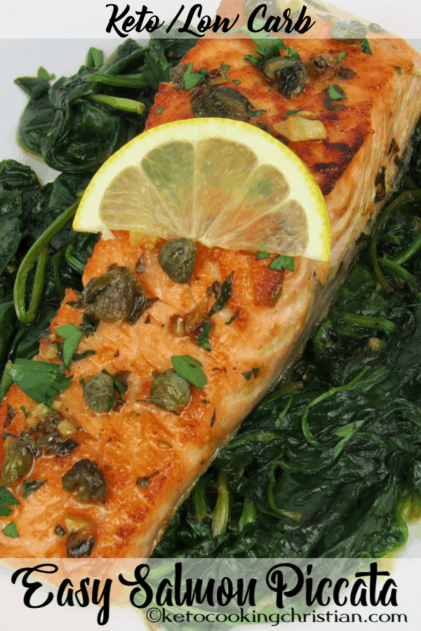 salmon on top of a bad of fresh spinach with a lemon slice