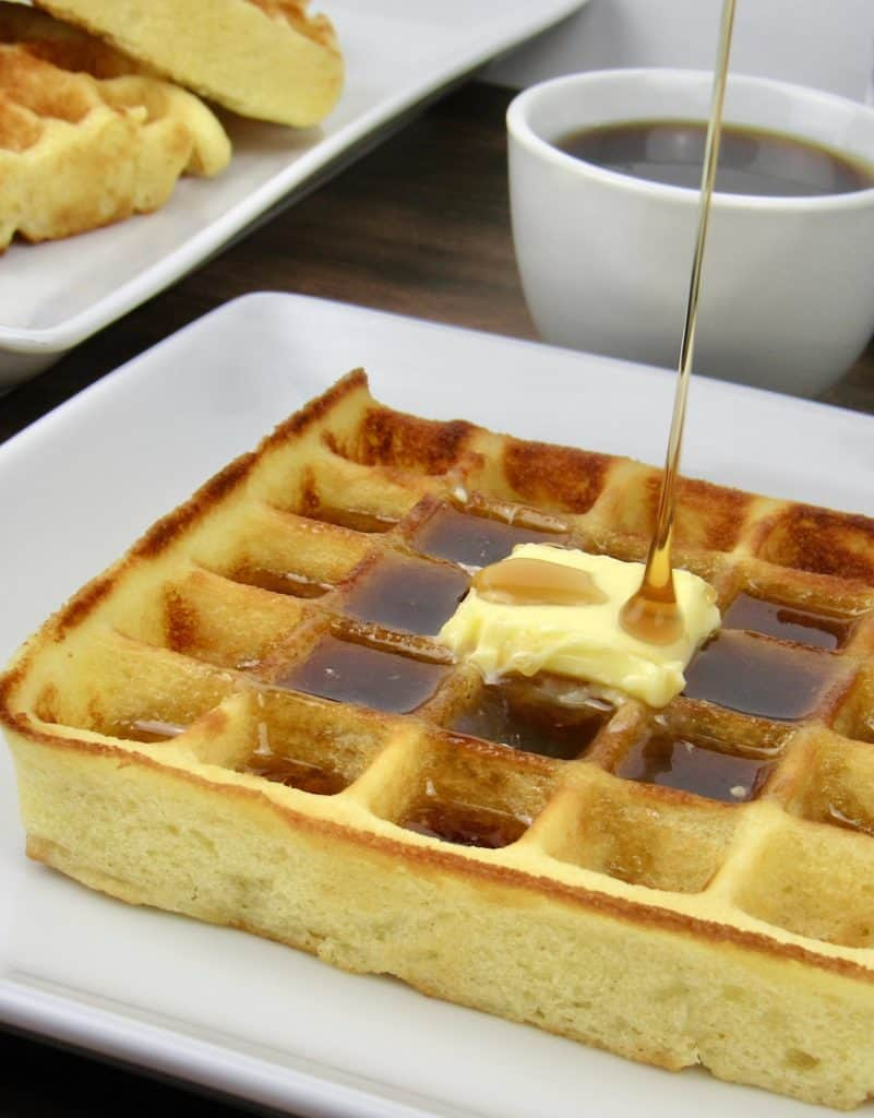 waffle on white plate with butter and syrup being poured on top