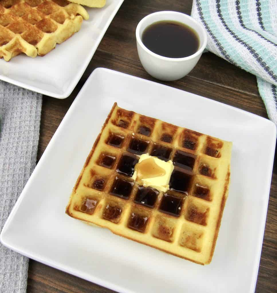 waffle on white plate with butter and syrup on top