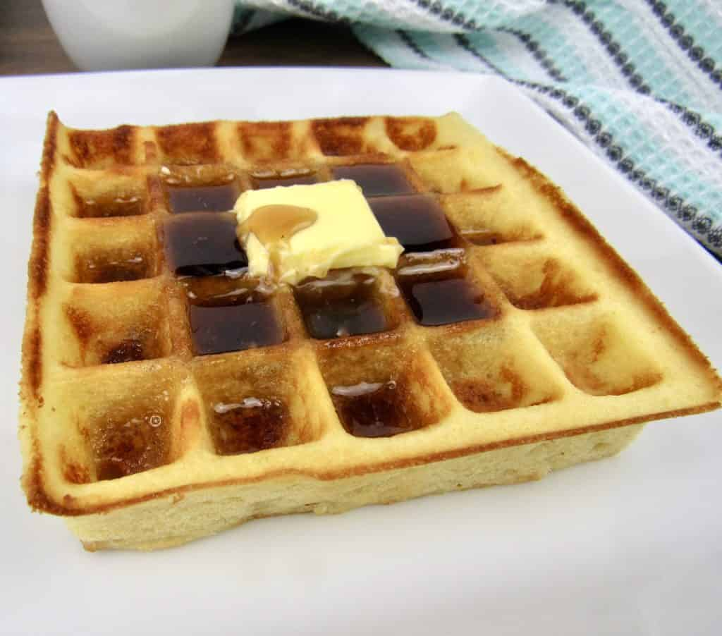 closeup of waffle on white plate with butter and syrup on top