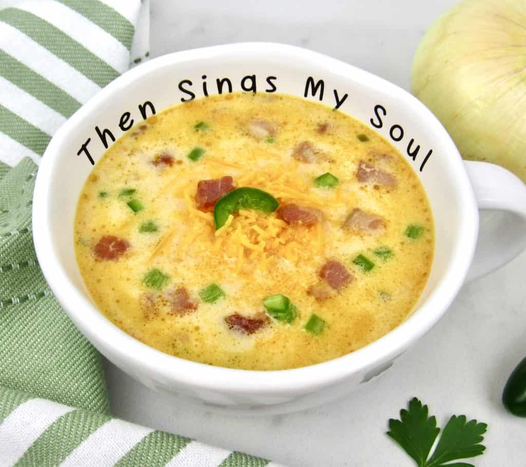 closeup of bowl of jalapeno popper soup with cheese on top