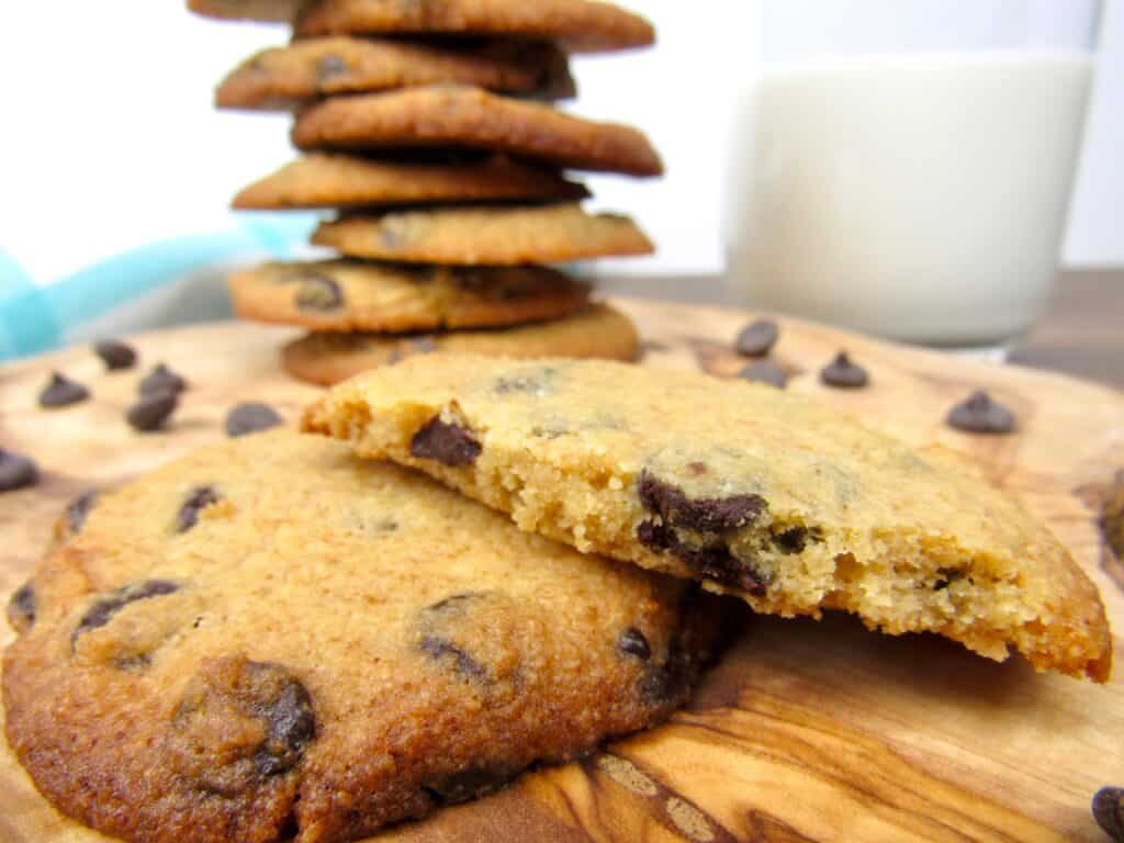 closeup of broken chocolate chip cookies with stack in background
