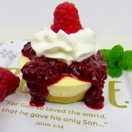 cheesecake with raspberry sauce and whip cream on top