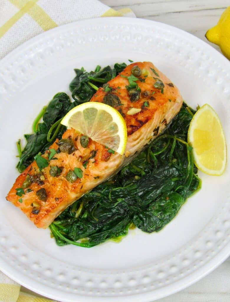 overhead view of salmon on top of spinach on a white plate with lemon slice on top