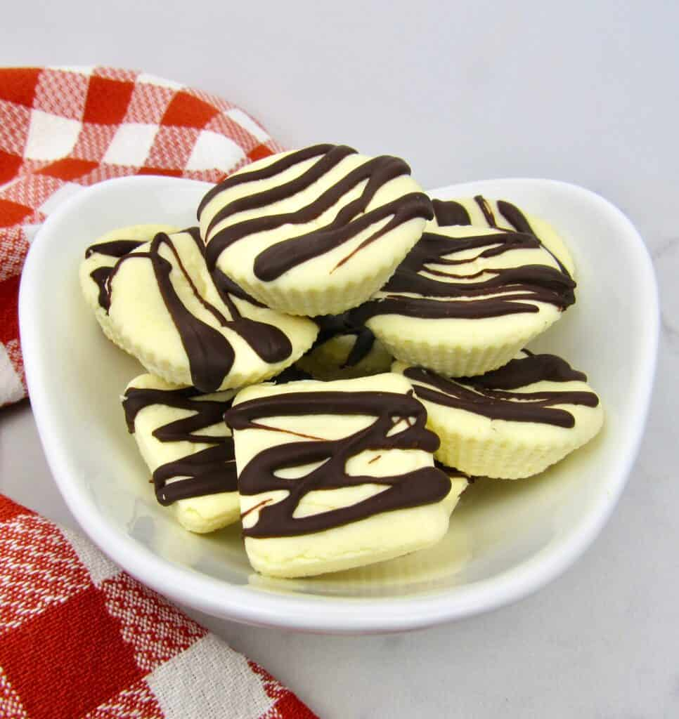 cheesecake fat bombs with chocolate drizzle in white bowl
