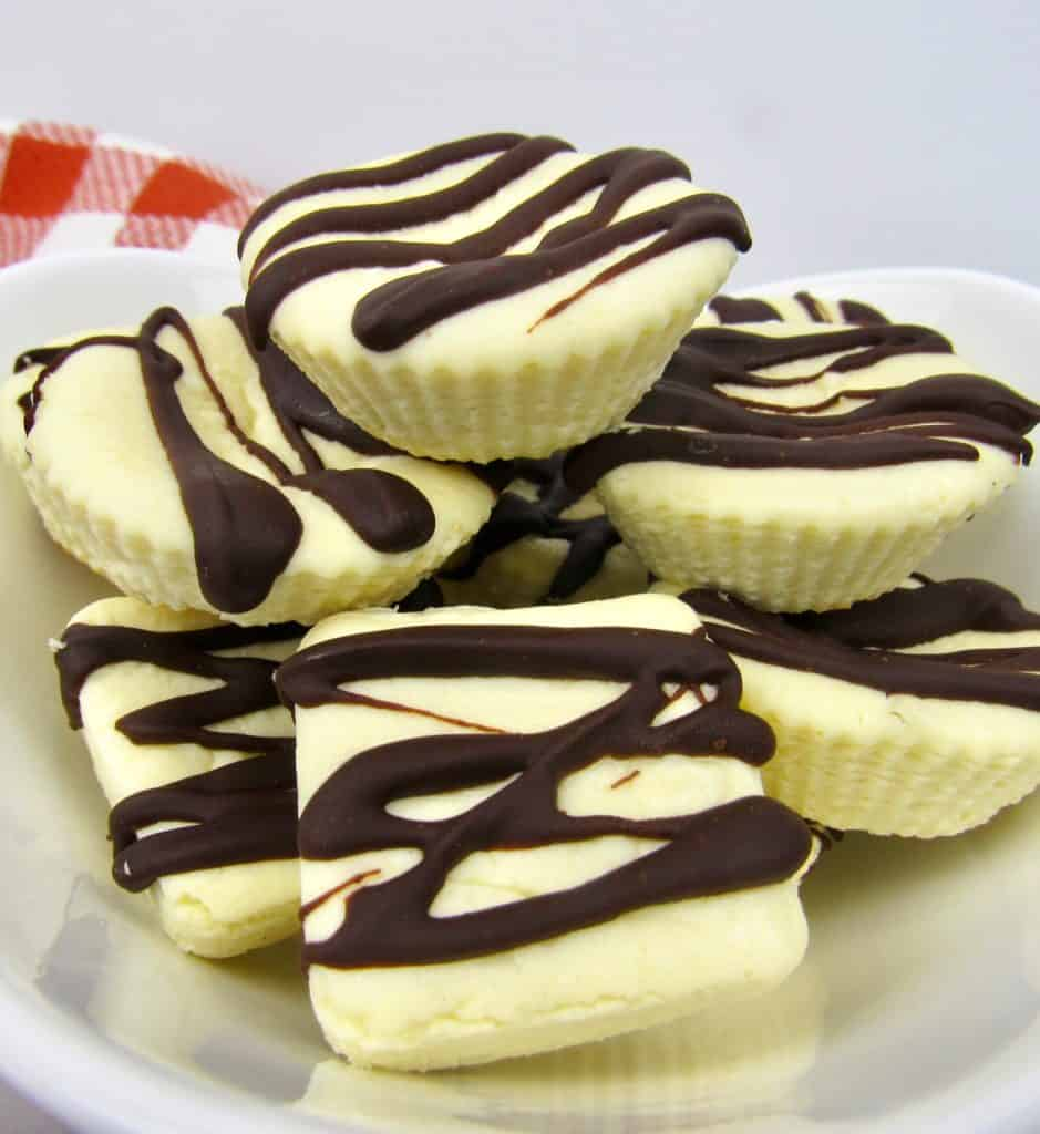 Cheesecake Fat Bombs in white bowl with chocolate drizzle on top