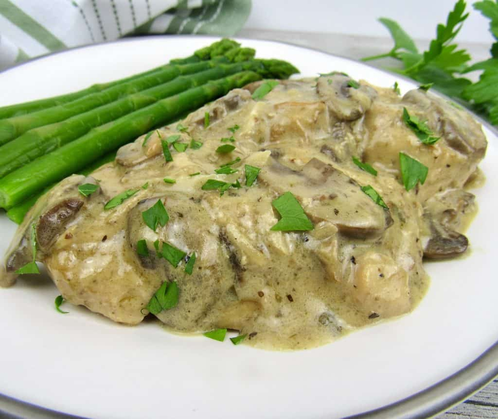 chicken marsala on white plate with asparagus