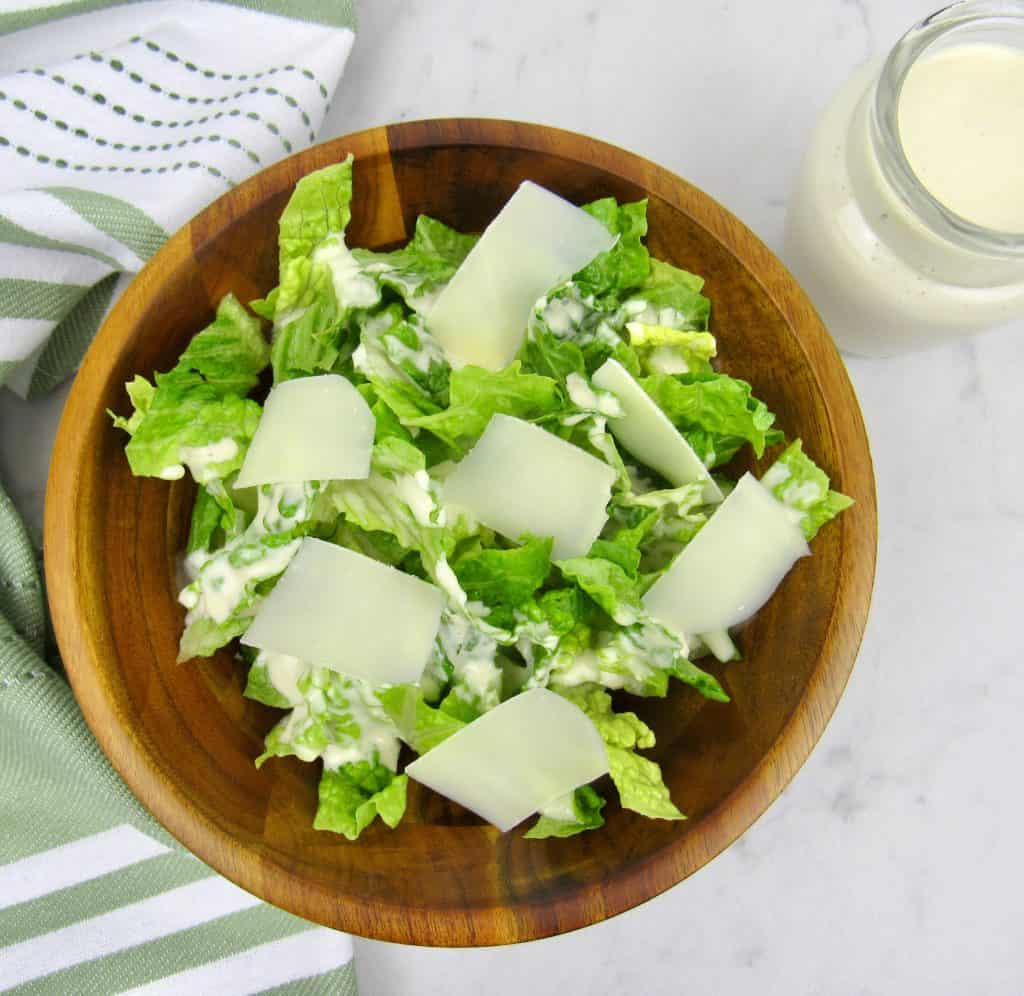 caesar salad with dressing in glass jar on the side