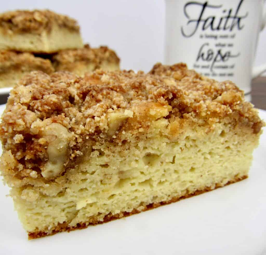 closeup of coffee cake with cup of coffee in background