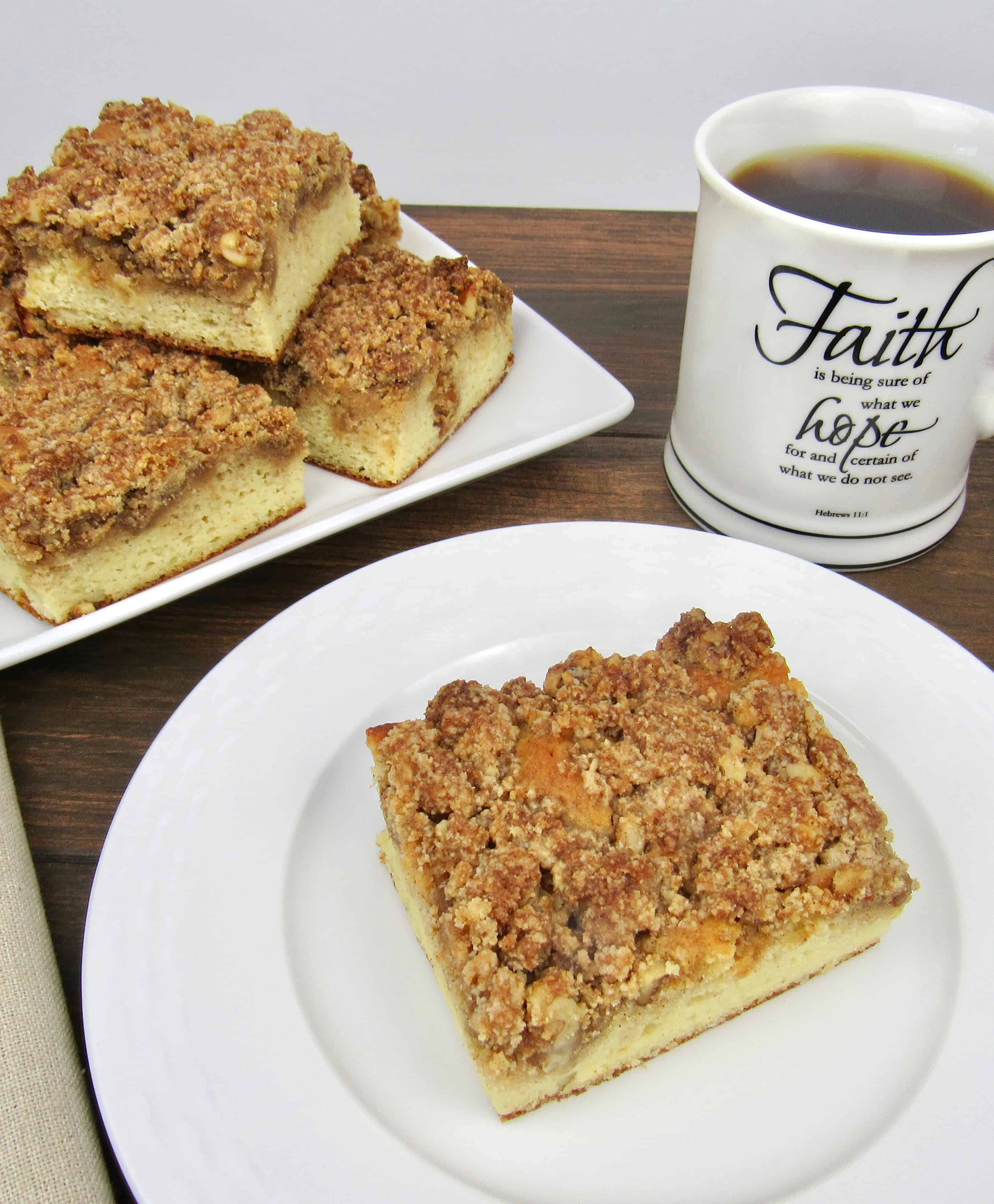 slice of coffee cake on white plate, cup of coffee and crumb cake slices in background