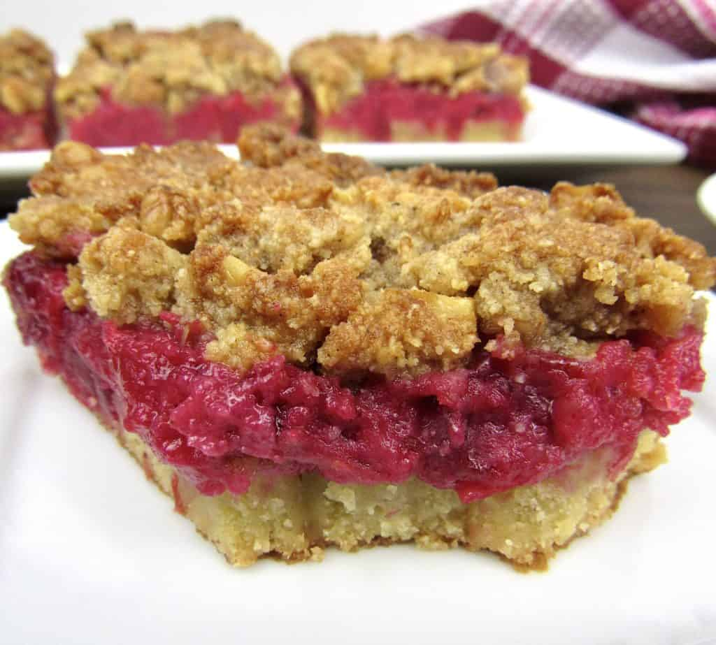 closeup of cranberry walnut crumble bar on white plate