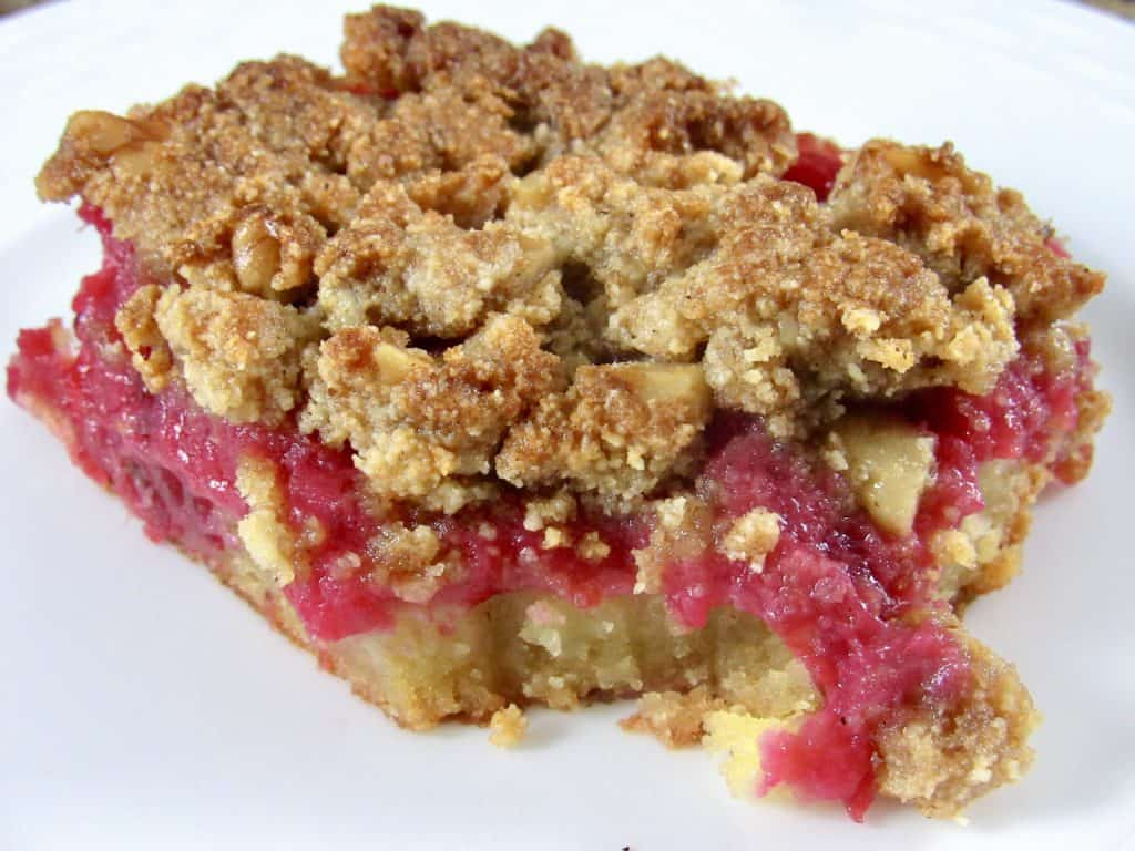 closeup of a cranberry walnut crumble bar on white plate