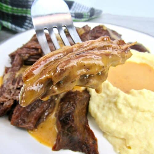 closeup of pot roast on fork with gravy dripping