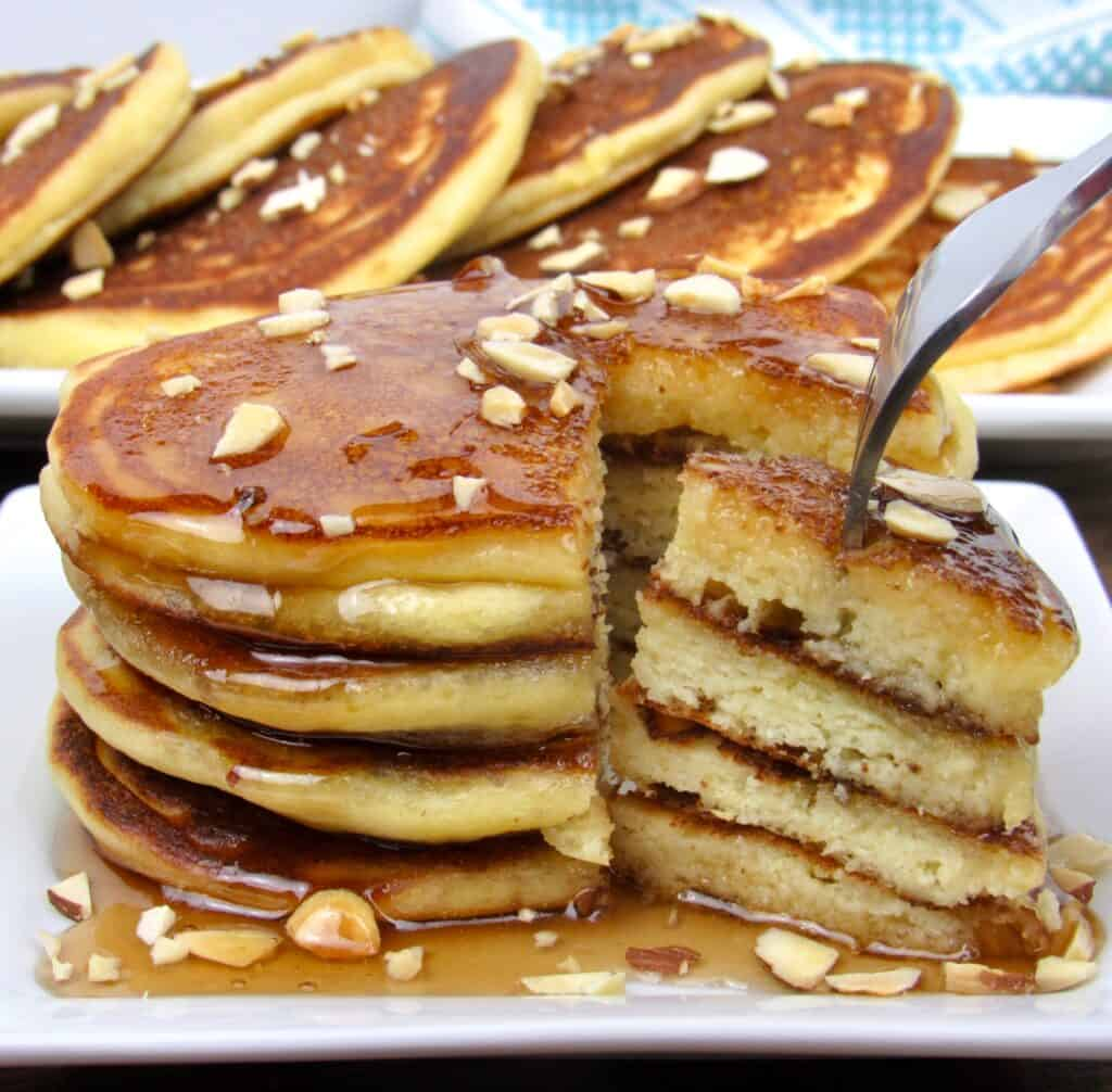 stack of pancakes with syrup being cut into with a fork
