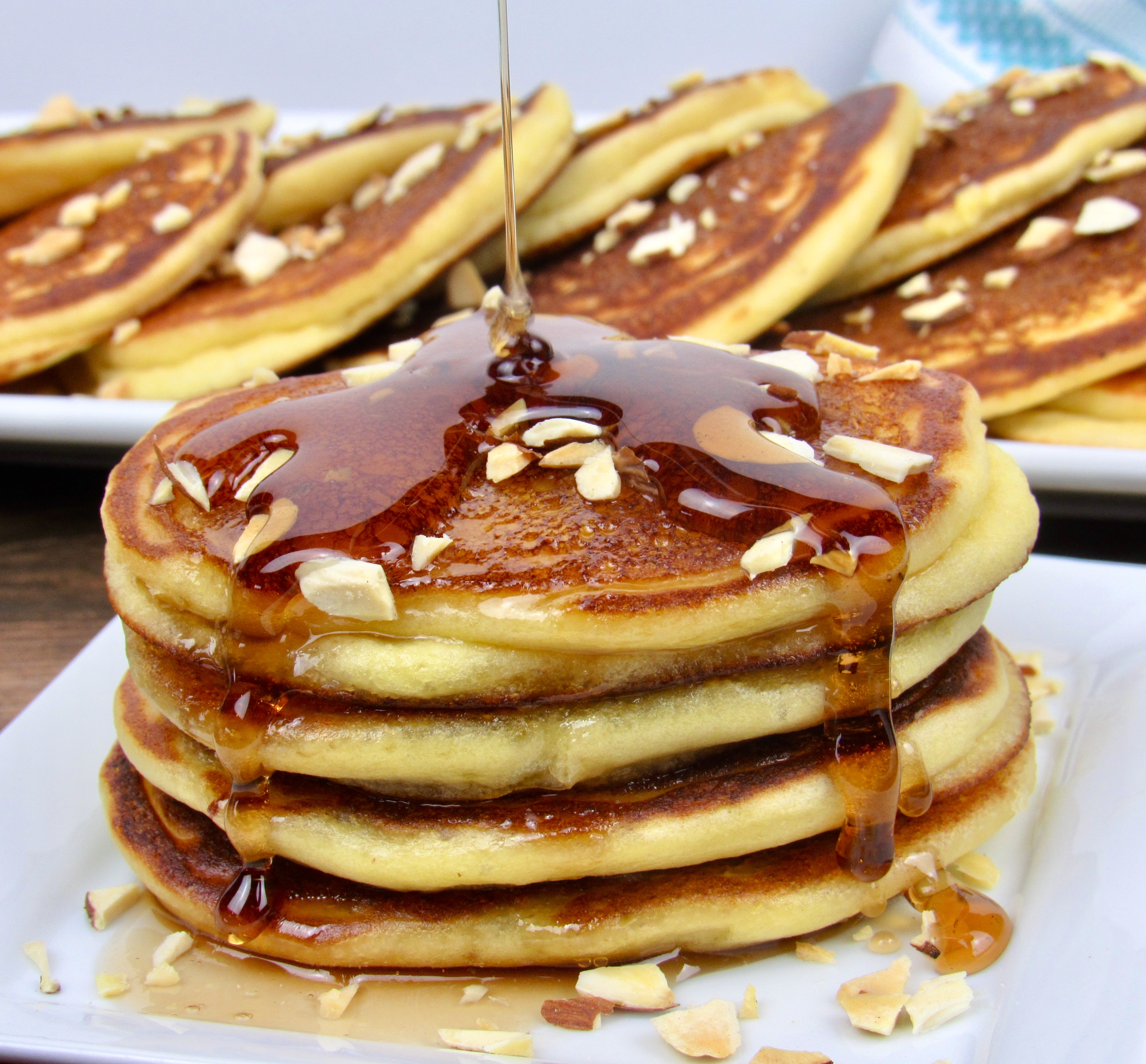 stack of pancakes with syrup being poured over the top