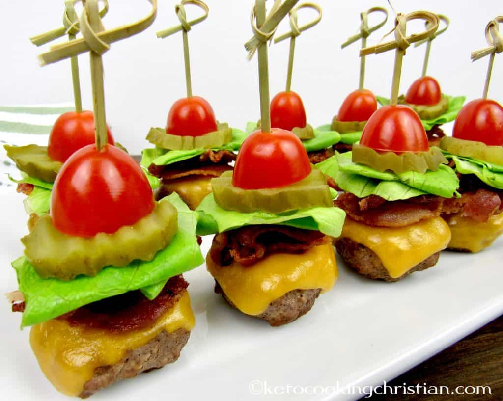 mini burgers with bacon cheese lettuce tomato with a skewer through the center