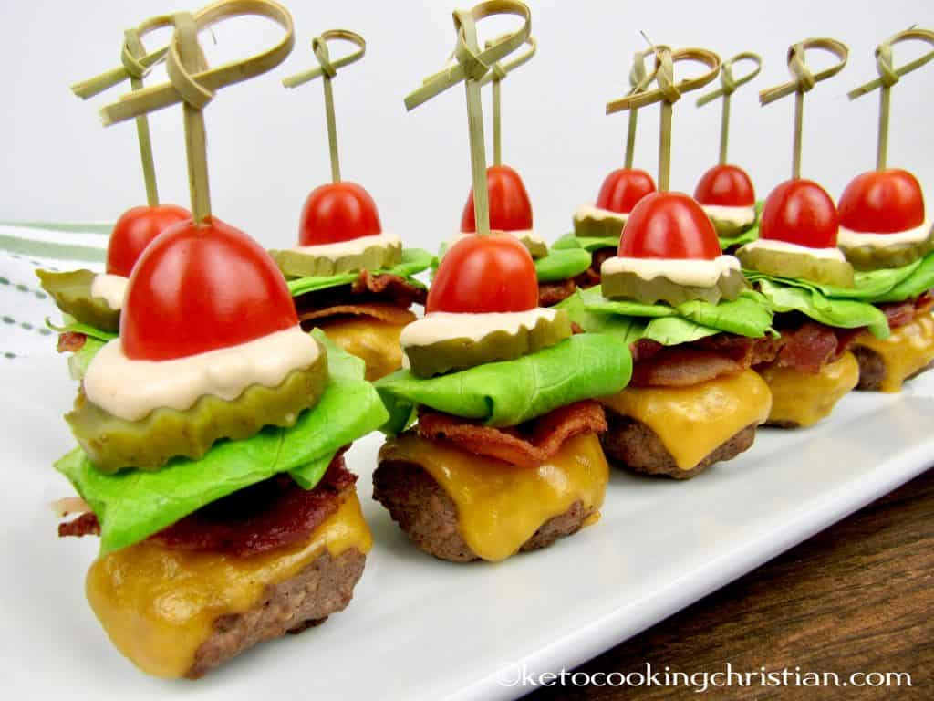 mini burgers with bacon cheese lettuce tomato and thousand island dressing with a skewer through the center