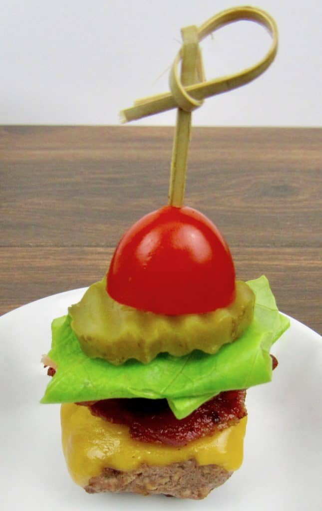 mini burger with bacon cheese lettuce tomato with a skewer through the center