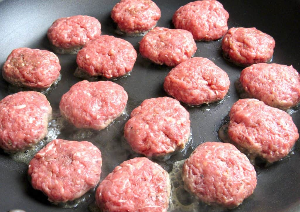 mini burgers cooking in a pan