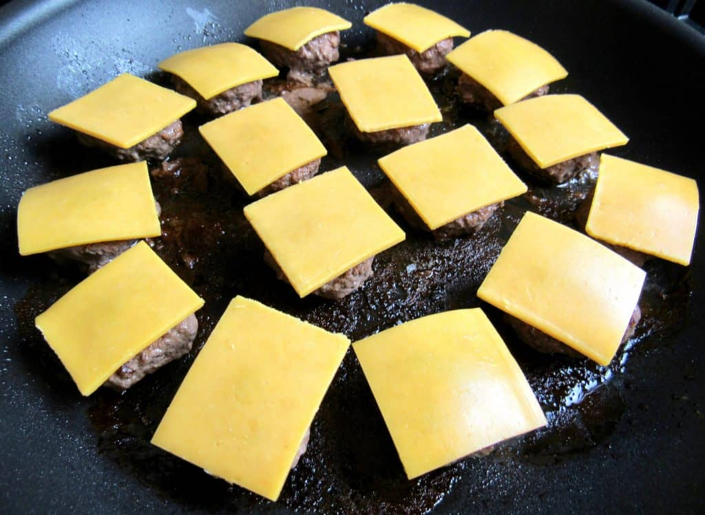burgers in a pan with cheese over the tops