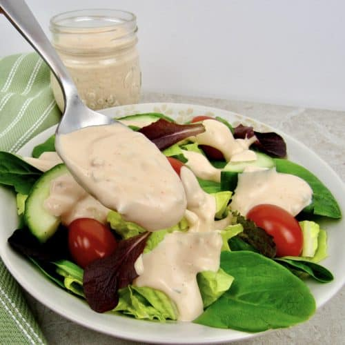 thousand island dressing being spooned over salad