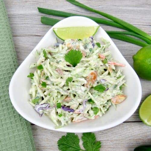 bowl of lime cilantro slaw with a slice of lime at the top of the bowl