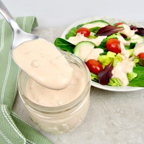 salad with thousand island dressing being pour on with a spoon
