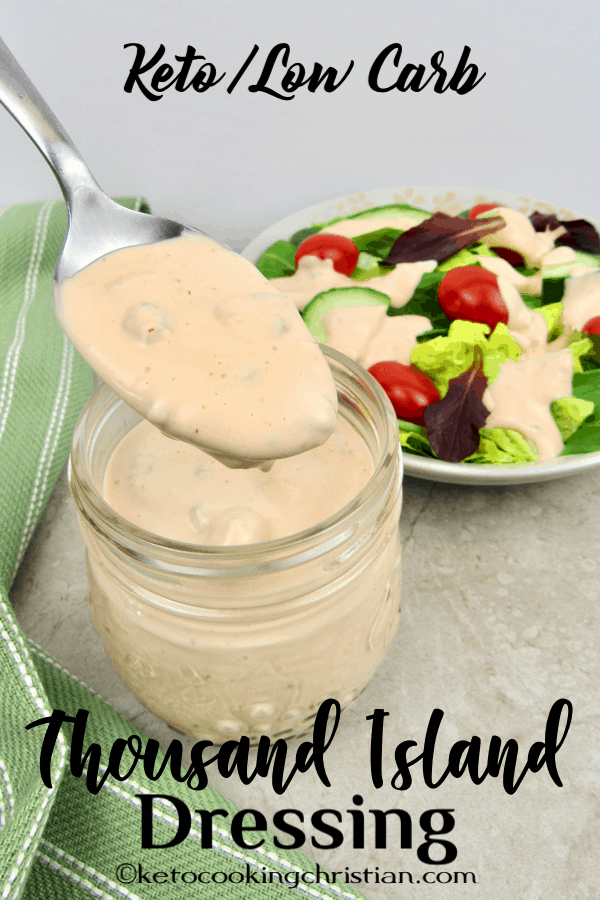 Spooning thousand island dressing out of a jar with a salad in the background
