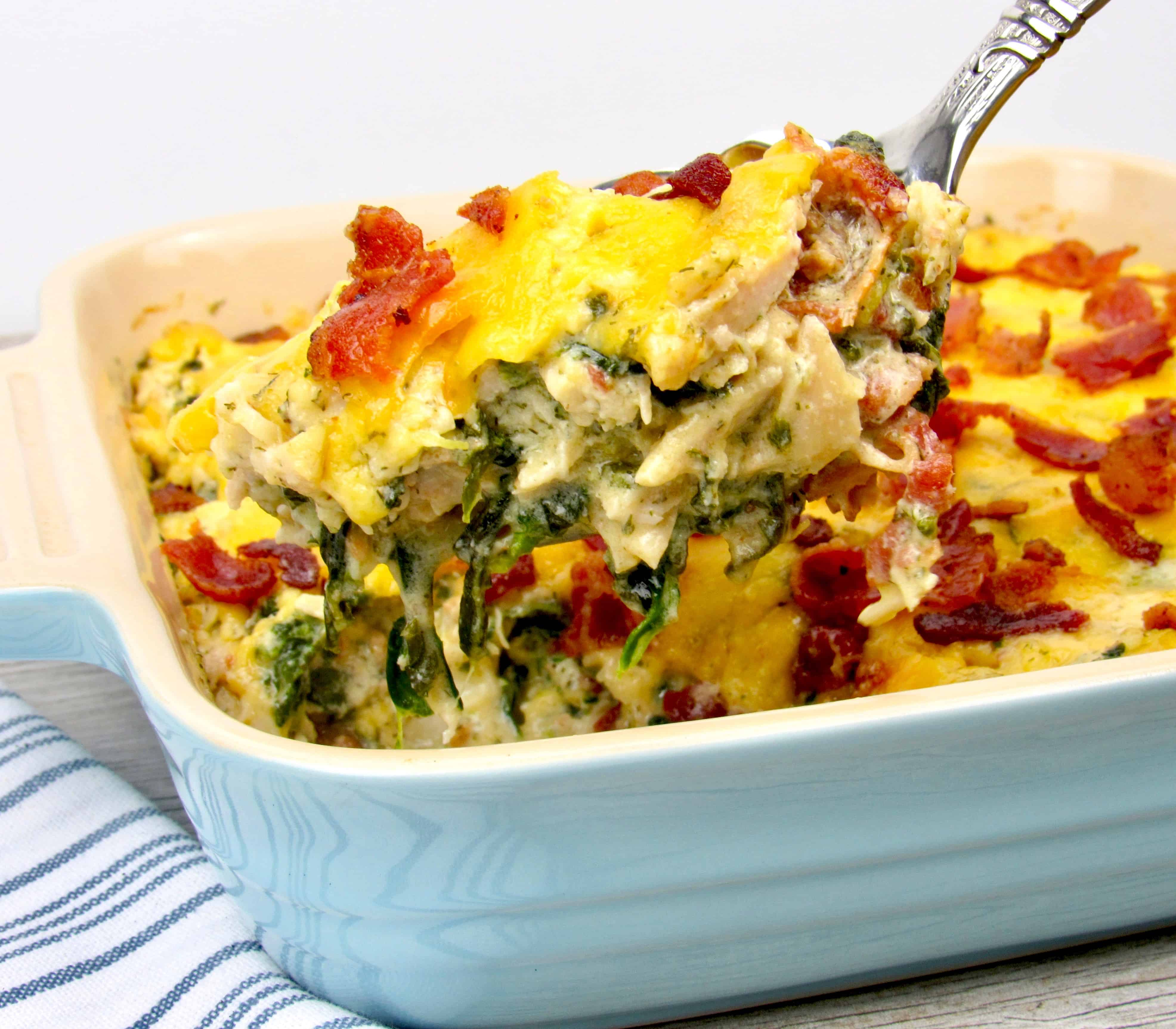 ladle spooning out chicken ranch casserole with cheese and bacon on top