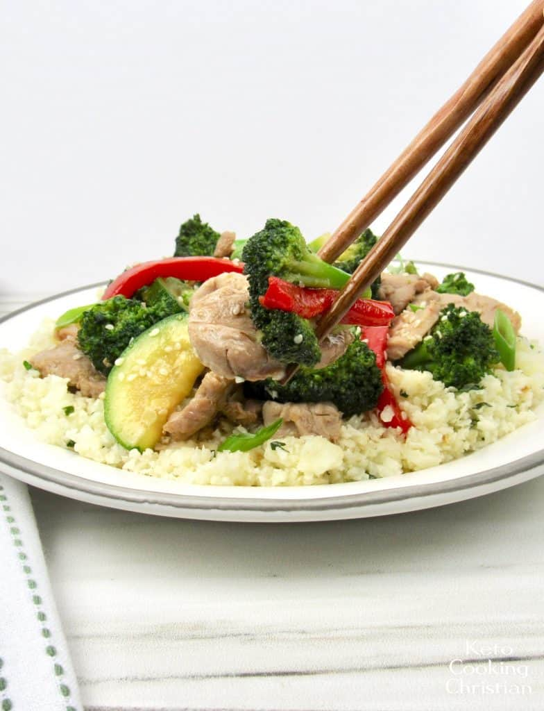plate of pork and veggies with chop sticks