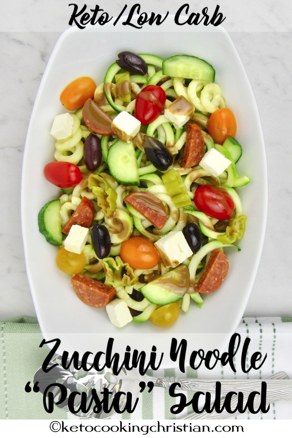 bowl of zucchini noodles with cut veggies over the top and a drizzle of balsamic dressing